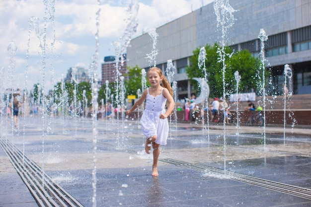 Little cute girl walking in open street fountain at hot sunny day