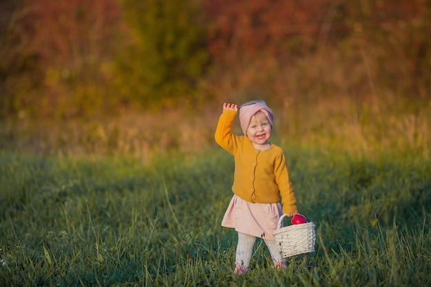 Little cute girl walks in the autumn garden, holds a basket with red apples. portrait of a happy girl in bright, autumn clothes. warm and bright autumn.