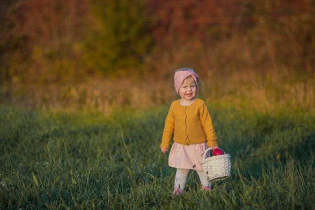 小さなかわいい女の子が秋の庭を歩き、赤いリンゴのバスケットを持っています。明るい秋の服を着た幸せな女の子の肖像画。暖かくて明るい秋。