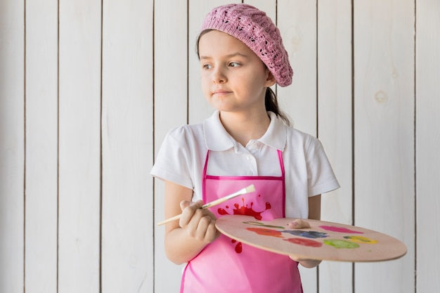 A little cute girl wearing pink woven hat holding paintbrush and paint palette