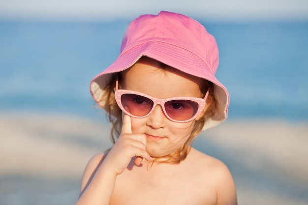 Little cute girl wearing sunglasses and summer pink hat standing near by the sea on summer vacation.