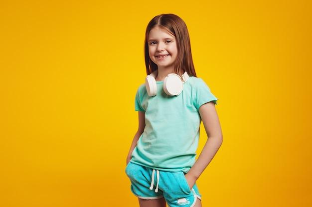 Маленькая милая девочка в белых наушниках на шее, держа руки в карманах