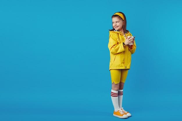 Маленькая милая девочка носит плащ, держит чашку с чаем на вынос и смотрит