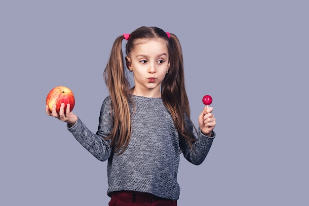 Маленькая милая девочка с конфетой и яблоком в руках. выбор концепции между здоровой и вредной пищей. изолированные на серой поверхности
