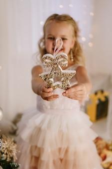 Маленькая милая девочка с рождественской звездой в руках
