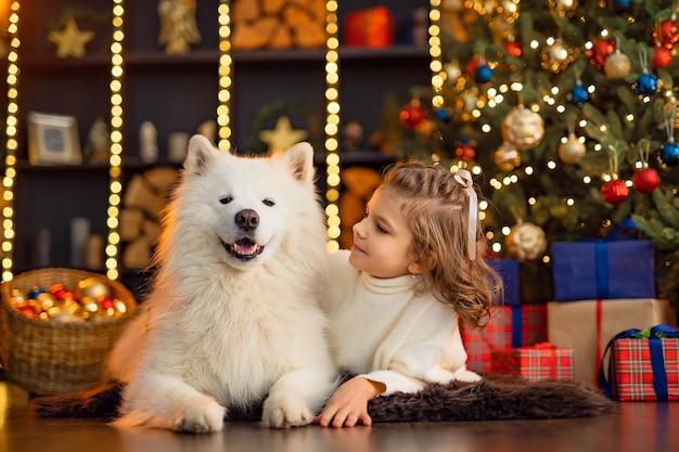 クリスマスツリーの近くに白いマラミュート犬と小さなかわいい女の子。