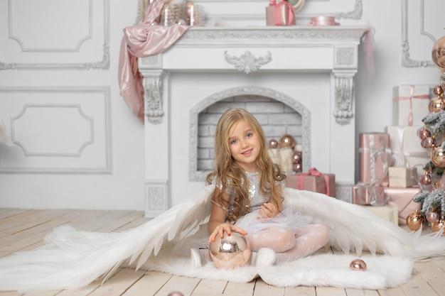 クリスマスツリーの隣のスタジオで天使の羽を持つブロンドの髪の少女
