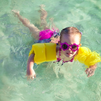 Little cute girl with diving in the sea in nice sunglasses