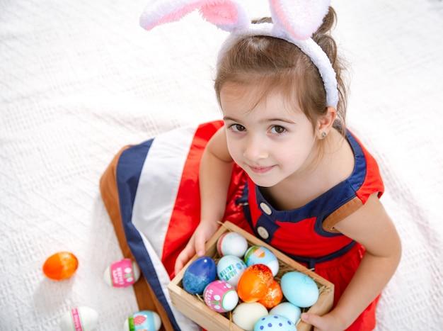 Маленькая милая девочка с пасхальными яйцами и ушками зайчика в красивом ярком платье.