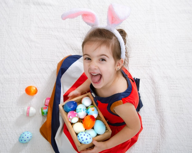 Little cute girl with easter eggs and bunny ears in a beautiful bright dress.