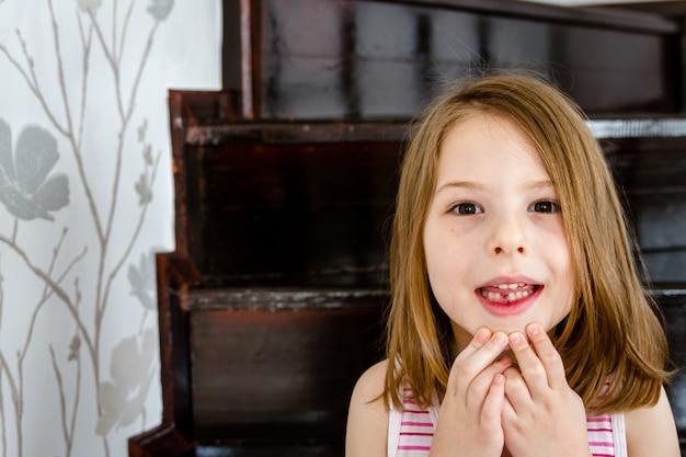 Маленькая милая девочка с первым потерянным молочным зубом