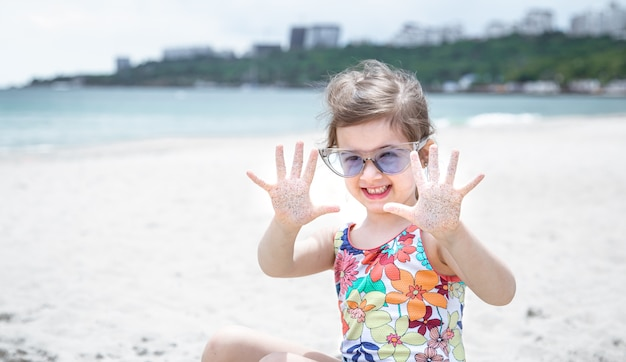 A little cute girl with glasses is playing in the sand on the beach by the sea.