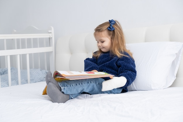 本を読んでベッドに座っている石膏の手を持つ小さなかわいい女の子。