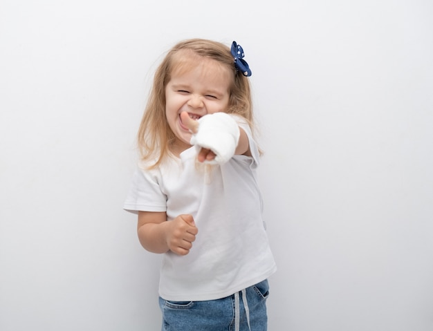 Little cute girl with hand in plaster showing the class on white background.