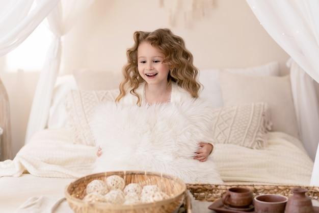枕を抱き、遊んで、笑顔の長い髪の小さなかわいい女の子 Premium写真