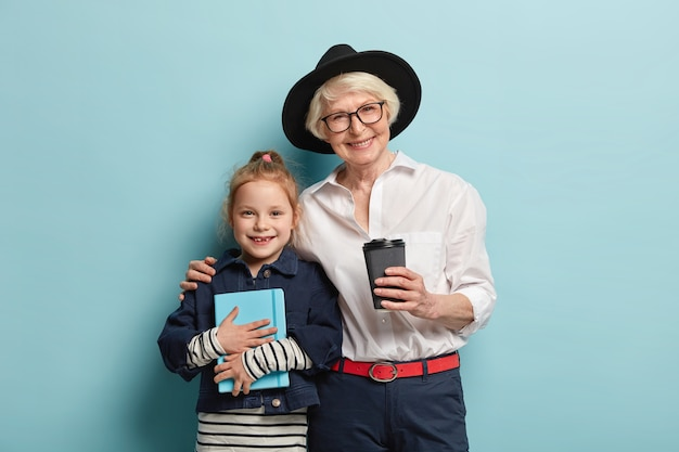 Little cute girl with notepad, spends free time together with grandma, being in good mood, drink takeaway coffee, cuddle. smiling elderly teacher embraces small kid pupil, study together indoor