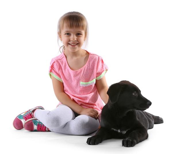 白で隔離される子犬とかわいい女の子