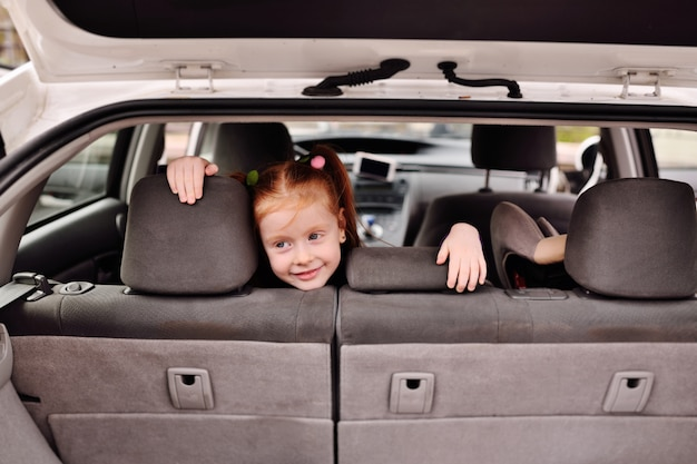 Little cute girl with red hair smiling in the interior of a car interior