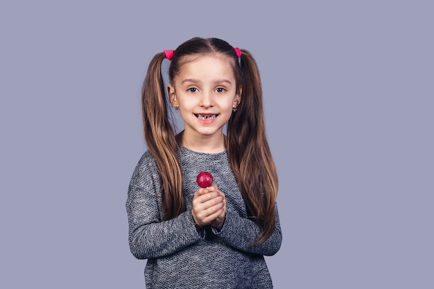 A little cute girl with a red lollipop in her hands shows her spoiled teeth. the concept of tooth decay due to the abuse of candy. isolated on gray background