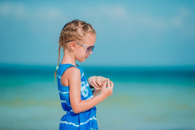 Little cute girl with seashell in hands at tropical beach.