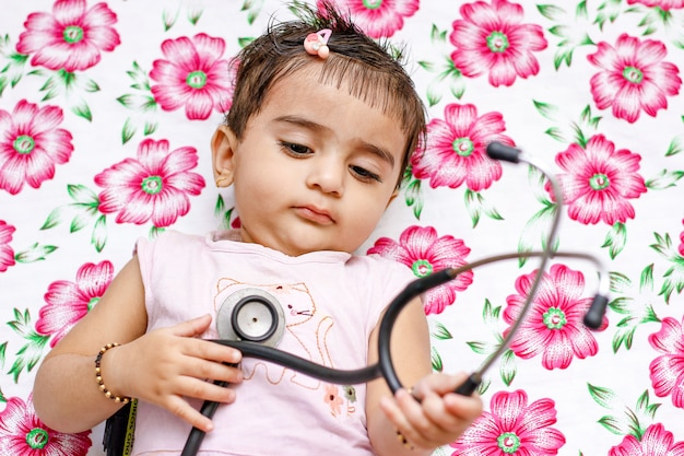 Little cute girl with stethoscope sitting on carpet