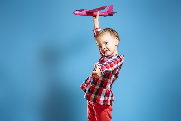 Little cute girl with a toy plane showing her thumb up.