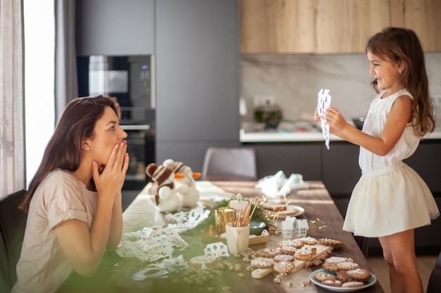 Little cute girl and young beautiful woman cut snowflakes from white paper. gingerbread and cocoa with marshmallows. the concept of preparation for the new year and christmas.