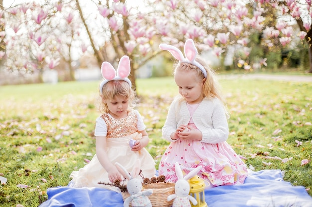Little cute girls are sitting on the grass near the mogolia. girls in costumes easter bunnies. spring.