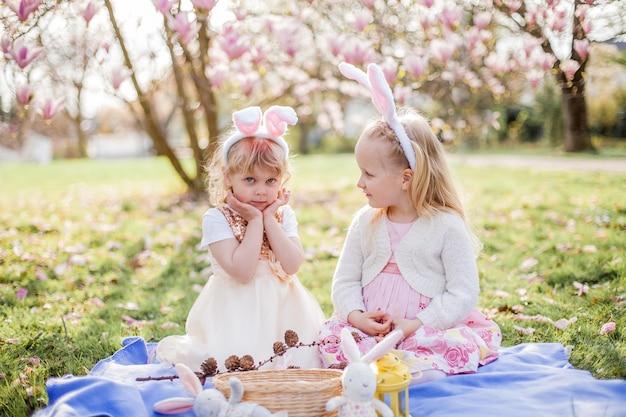 작은 귀여운 소녀는 mogolia 근처 잔디에 앉아있다. 의상 부활절 토끼 소녀. 봄.