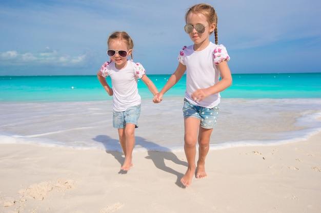 Little cute girls enjoy their summer vacation on the beach