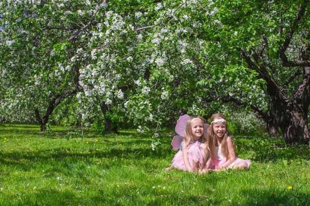 Маленькие милые девочки в цветущем яблоневом саду