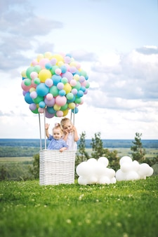 Little cute girls kids beautiful and happy with balloon airship on blue sky background with clouds
