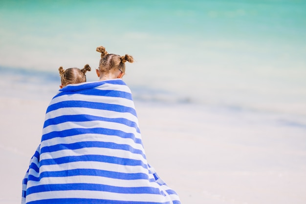 熱帯のビーチでタオルに包まれたかわいい女の子。ビーチでの休暇の子供たち