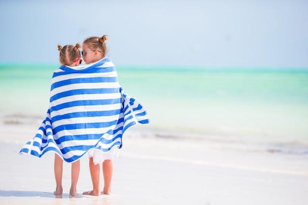 열 대 해변에서 수건에 싸여 귀여운 소녀. 해변 휴가에 아이