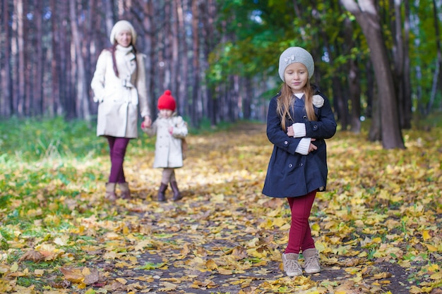 Little cute girls and young mother in autumn park have fun