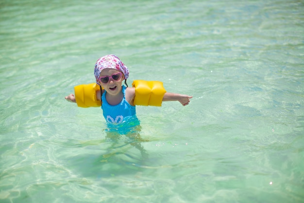 Little cute happy girl at swimsuit has fun in the sea