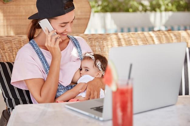 小さなかわいい乳児が母親の胸から餌をやる。陽気な若いお母さんが携帯電話で友達と話し、子供を気遣う。