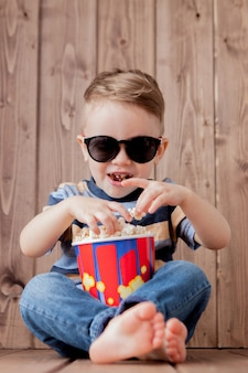 小さなかわいい子供男の子2-3歳、ポップコーンのバケツを持って、木製の背景にファーストフードを食べる3 d imaxシネマグラス。子供の幼年期のライフスタイルコンセプト。