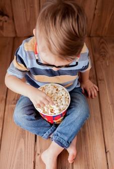 小さなかわいい子供男の子2〜3歳、ポップコーンのバケツを保持している3dimaxシネマメガネ