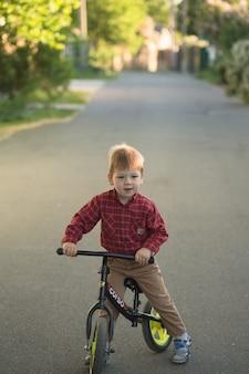 Маленький милый мальчик малыш на велосипеде на лето или осенний день. здоровый счастливый ребенок с удовольствием с езда на велосипеде на велосипеде.