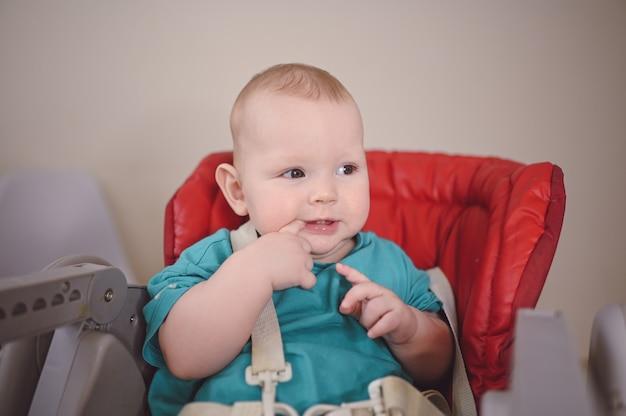Маленький милый новорожденный ребенок сидит на стульчике для кормления
