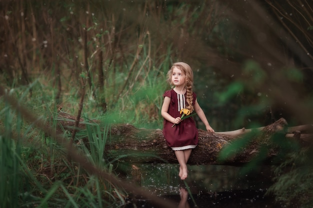Little cute pensive girl sitting on log by the stream