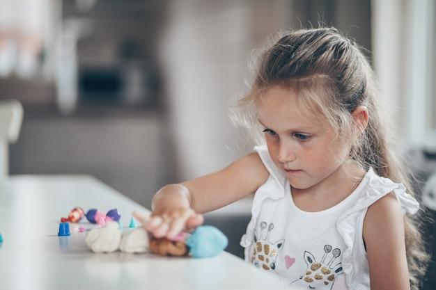 学校の準備をする粘土の数字で教育ゲームをプレイするかわいい幼児子供女の子