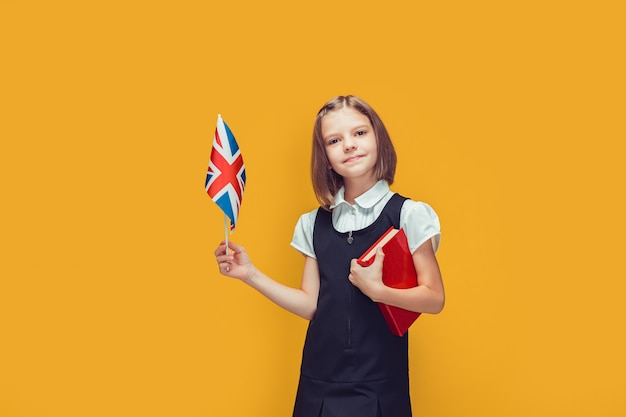 Little cute pupil holding united kingdom flag and book studying english on yellow background