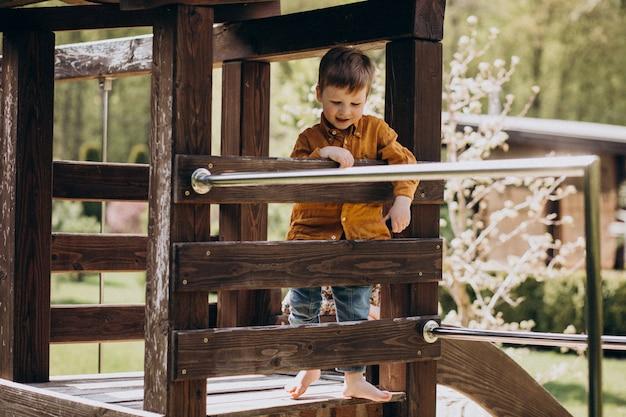 Маленький милый рыжий мальчик с удовольствием на заднем дворе
