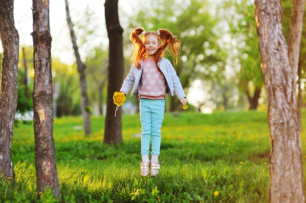 A little cute red-haired girl on the background of a field of dandelions and greenery.