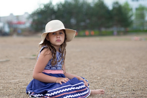 Little cute sad caucasian girl sitting in summer hat and beautiful blue dress on the beach. looking up. high quality photo