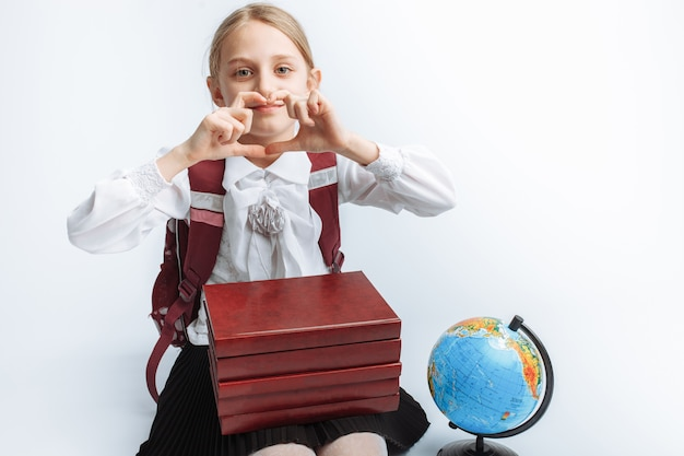 Little cute schoolgirl girl sitting with books and globe, smiling and showing heart, white wall