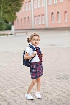 학교 가방 배낭과 제복을 입은 작은 귀여운 여학생