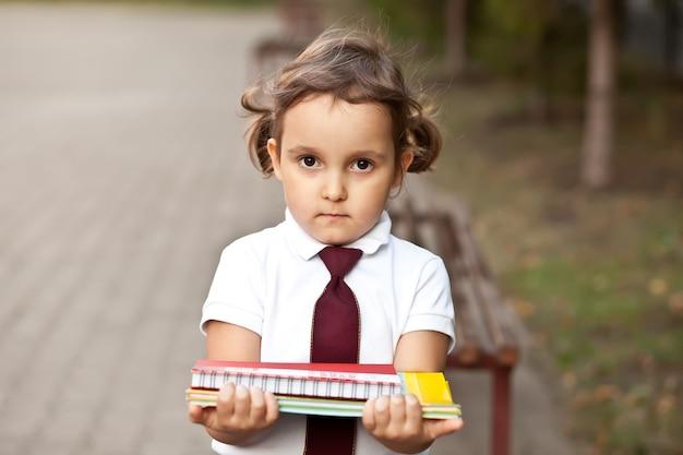 학교 책과 제복을 입은 작은 귀여운 여학생